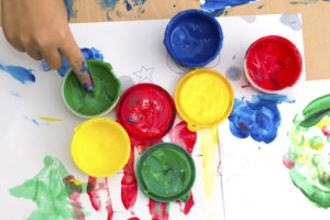 colorful finger paints with children hand on a table